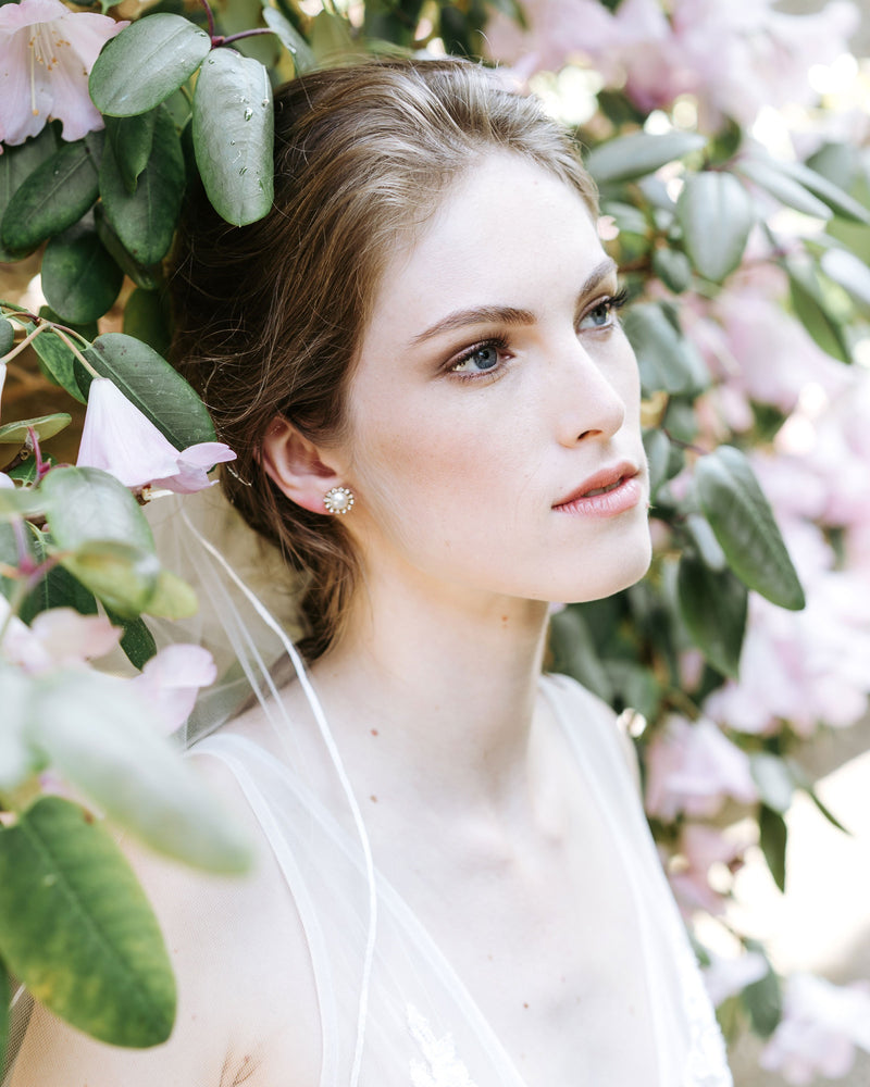 model wearing swarovski crystal halo pearl stud earrings in gold cream