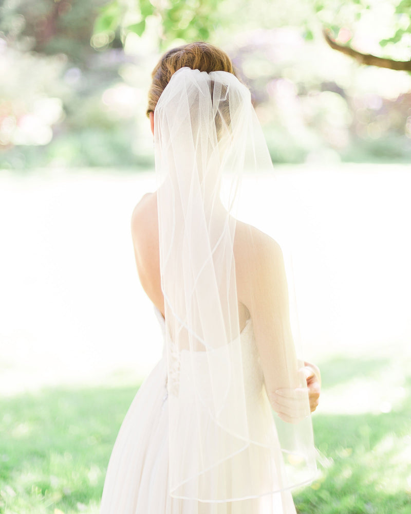 "Model wearing short veil with delicate 3/8"" satin ribbon edge"
