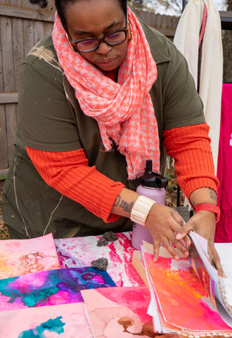 Naima Lowe leafing through a pile of colorful drawings.