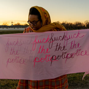 "Naima Lowe, wearing a yellow headscarf, black glasses and a black, red and yellow plaid dress, stands in a large clearing holding a light pink scarf which is decorated with the phrase ""fuck the police"" 5 times, overlapping in different shades of pink"