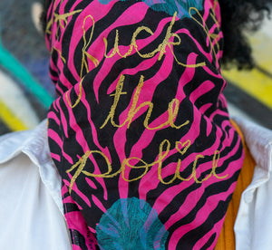 "A person with dark curly hair is wearing a pink and black zebra-stripe bandanna pulled up over their face. Blue abstract shapes made with thin lines are visible at the top and bottom of the bandanna. There is gold cursive handwriting spelling out the words ""Fuck the Police"", with the ""i"" in ""police"" being dotted with a heart."