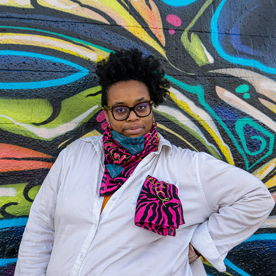 Naima Lowe, curly hair standing up, standing in front of a wall with large mural, wearing a white button-down shirt. She is wearing one pink and black zebra-stripe bandanna around her neck, and has one tucked into the shirt pocket. Each bandanna has gold cursive writing partially visible. The bandanna around her neck also has blue abstract shapes made of thin lines.