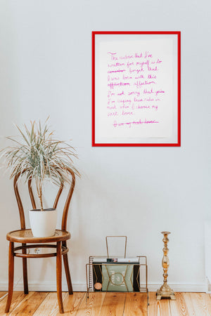 The art print in a thin red frame hanging on the upper right side of cream colored wall. A brass candlestick, bronze magazine holder with a black and light green magazine inside sit on a hardwood floor below the frame. The wall has simple molding at the edges. Next to the magazine holder is a small tropical plant sitting on a polished wooden chair.