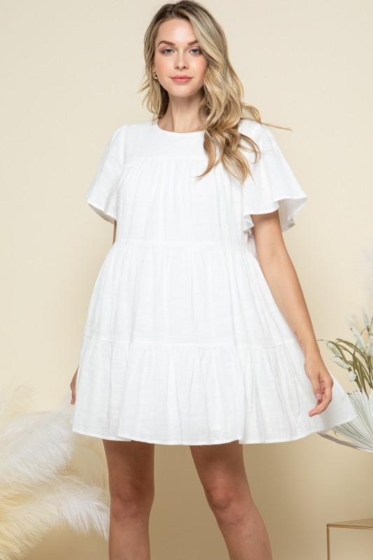 White mini dress with tiered detail and short sleeves.  Relaxed fit perfect for the beach or a casual weekend.