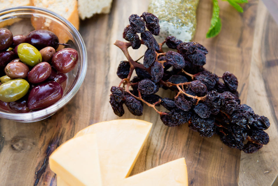 raisins on the vine raisin cluster on a wooden charcuterie board next cheese, olives and bread