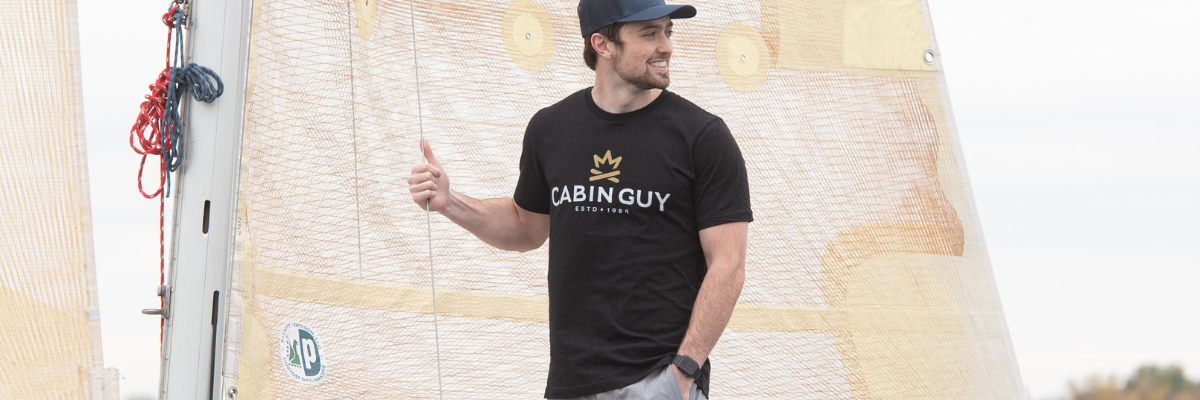 Guy with black Cabin Guy Tee on sailboat