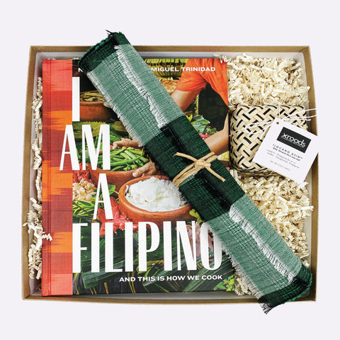 "Gift box featuring the Filipino cookbook ""I Am a Filipino"" by Nicole Ponseca, 2 green woven placemats, and an Ilocano salt"