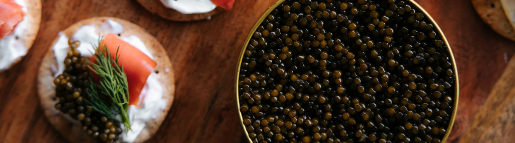 Picture of a big jar of caviar and a caviar toast next to it