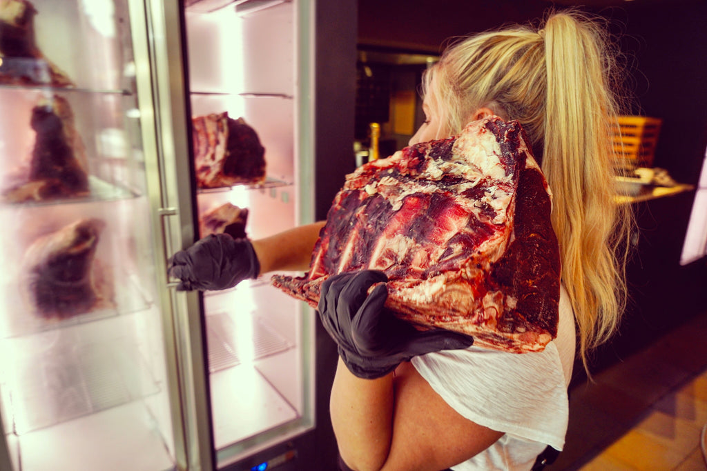 Picture of female waitress putting beef inside a dry aging cabinet
