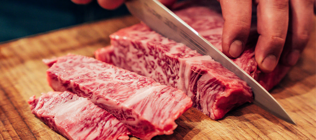 Picture of Wagyu A5 Kagoshima being cut on a wooden plate