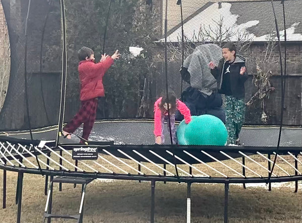 Photo of 3 kids playing in a trampoline in snow