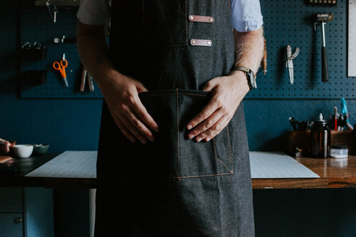 Leatherworker in apron in front of workshop