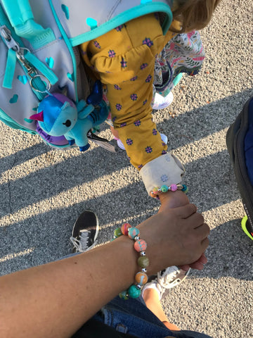 Young girl wearing a yellow dress, charm bracelet, and backpack as she holds her mother's hand on her way to the school bus