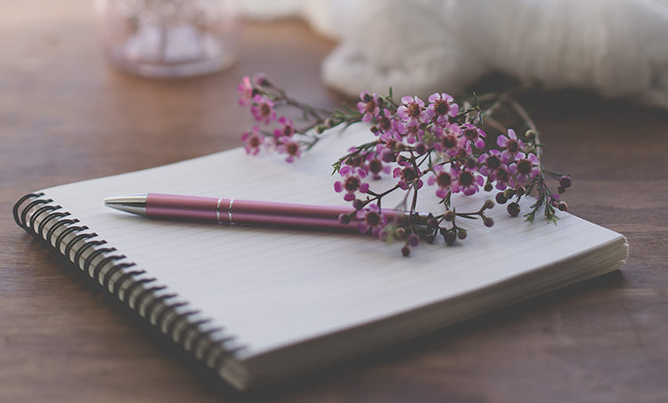 Purple baby's breath flower sitting on top of a white spiral-bound notebook with a pen