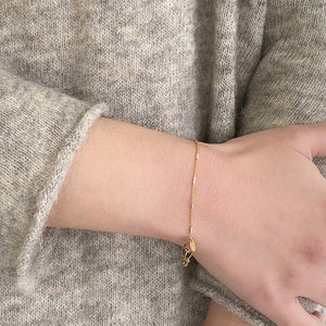Close-up of wrist weearing delicate gold chain bracelet, with silver rectangular bead accents.