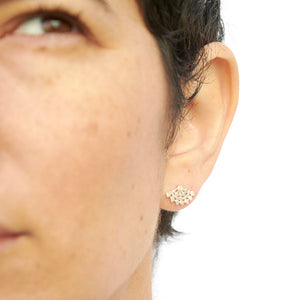 Close-up front view of woman wearing fan-shaped gold earrings with lace pattern.