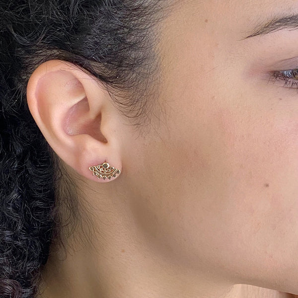 Close-up side view of woman wearing fan-shaped gold earrings with lace pattern.
