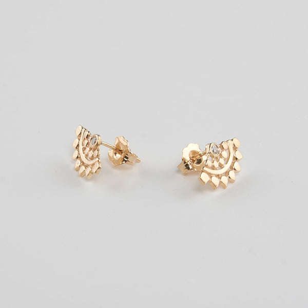 Pair of fan-shaped gold earrings with lace pattern, inset with small diamond, shown facing out.