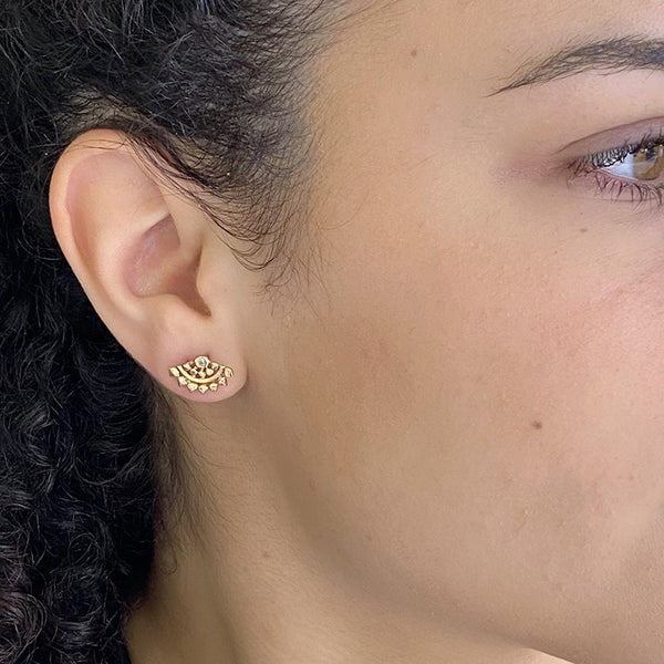 Close-up side view of woman wearing fan-shaped gold earrings with lace pattern, inset with small diamond.