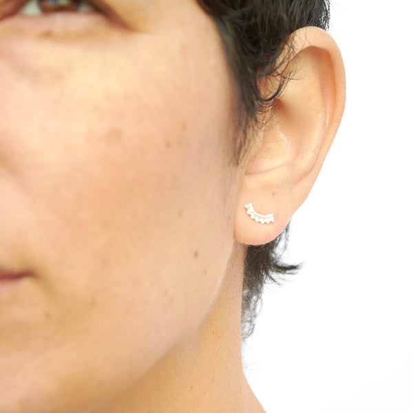 Close-up front view of woman wearing gold earrings, arc-shaped with little triangular beads.