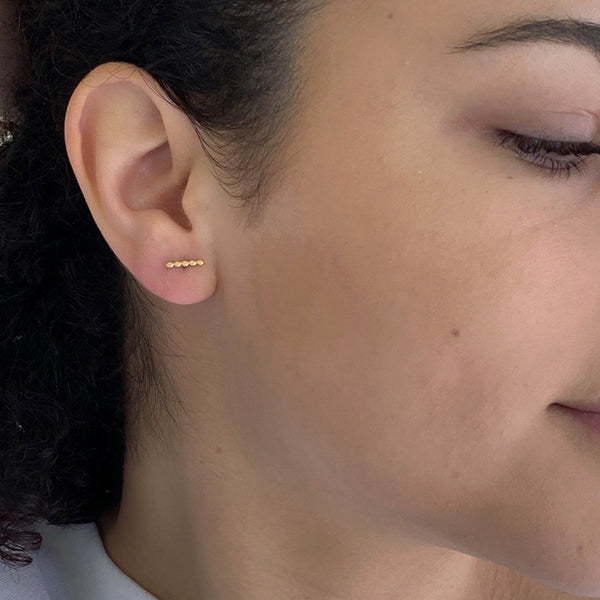 Close-up side view of woman wearing gold beaded bar earrings on earpost.