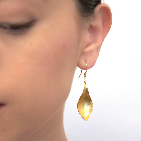 Close-up front view of woman wearing gold earrings, with curved simple leaf design.
