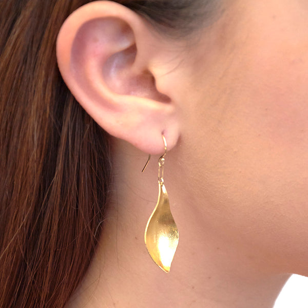 Close-up side view of woman wearing gold earrings, with curved simple leaf design.