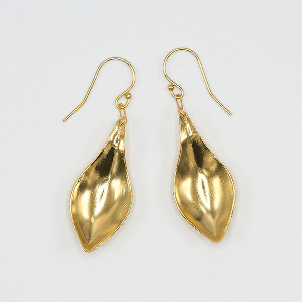 Pair of gold earrings, with curved simple leaf design, shown askew.
