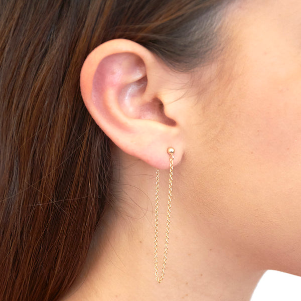 Side view of woman wearing gold earrings, long loop of delicate chain on a post.
