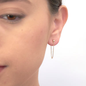 Front view of woman wearing gold earrings, short loop of delicate chain on a post.