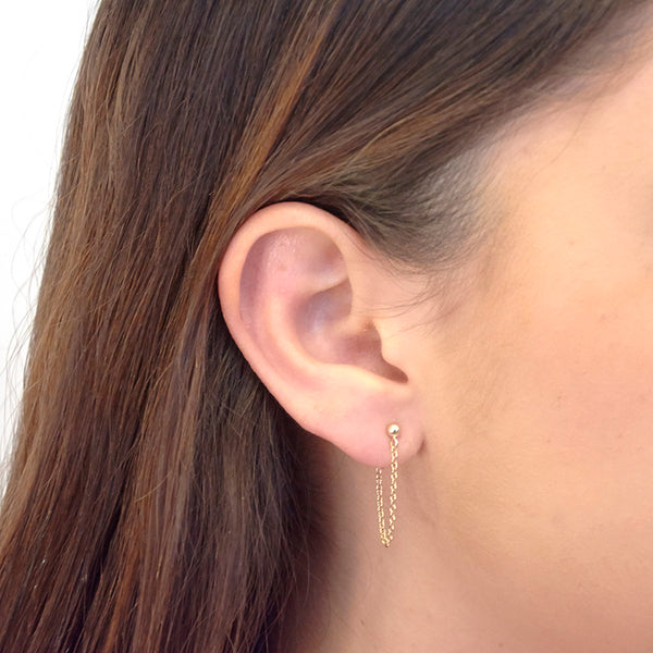 Side view of woman wearing gold earrings, short loop of delicate chain on a post.