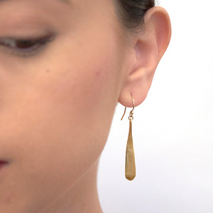 Close up front view of woman wearing gold earrings shaped like elongated teardrop.