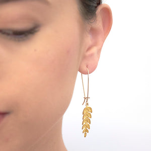 Close up front view of woman wearing gold fern leaf shaped earrings on long earwire.