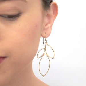 Close up front view of woman wearing gold earrings shaped like outline of group of leaves.
