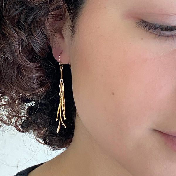 Close up front view of woman wearing gold earrings, with curved hanging frill design.