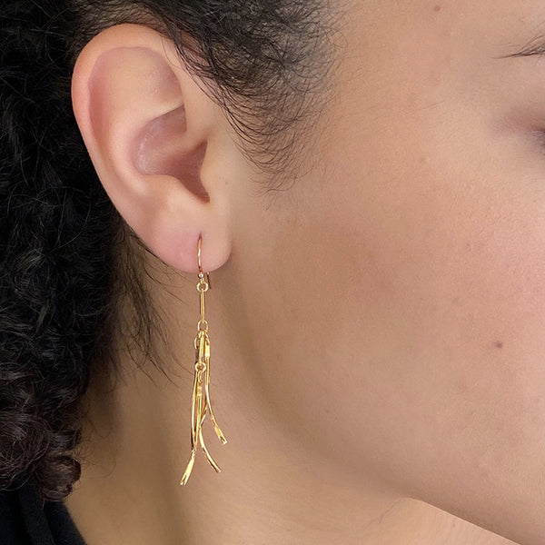 Close up side view of woman wearing gold earrings, with curved hanging frill design.