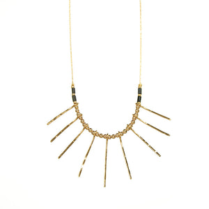 Delicate gold necklace, pendant of rays with gold beads in between and black tube beads at ends.