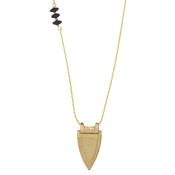 Gold necklace with brass shield shaped pendant and small black beads accents on chain.