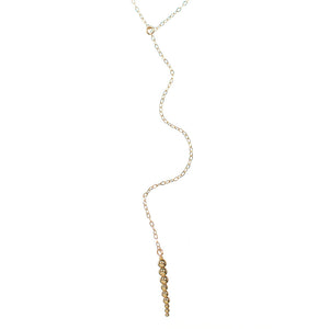 Close-up of delicate gold chain necklace with drop pendant of small gold beads.