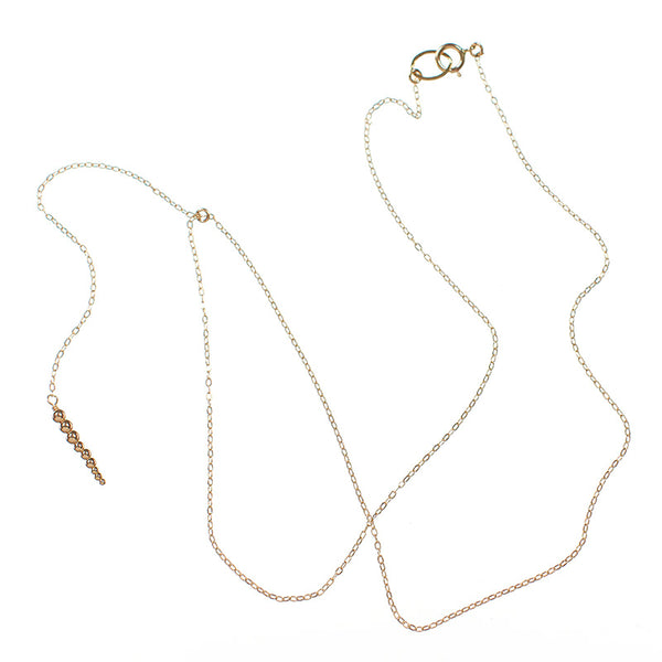 Delicate gold chain necklace with drop pendant of small gold beads, laid out showing clasp.