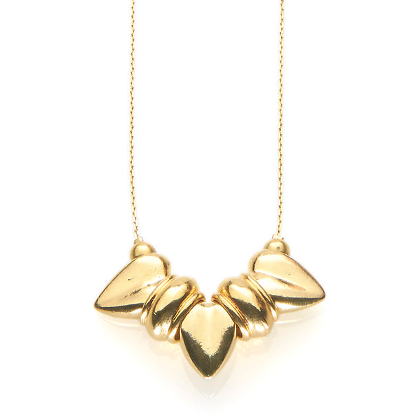Close-up of gold necklace, thin gold chain with pendant of three large heart-shaped beads.