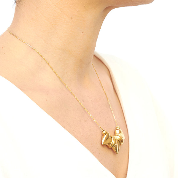 Woman wearing gold necklace, thin gold chain with pendant of three large heart-shaped beads, shown from side angle.
