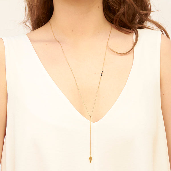 Woman wearing gold necklace, long arrow pendant, chain with black bead accents.