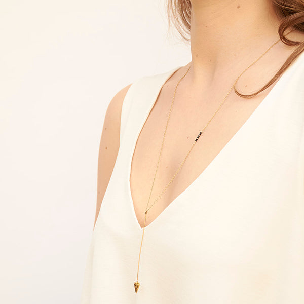 Woman wearing gold necklace, long arrow pendant, chain with black bead accents, shown from side angle.