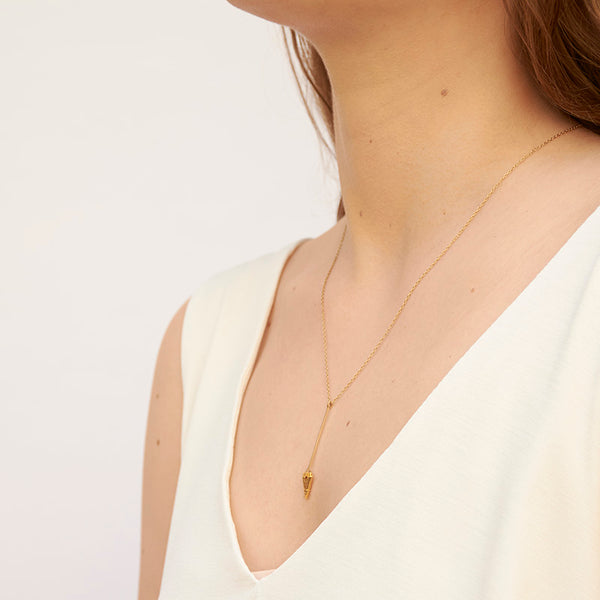 Woman wearing gold necklace, short arrow pendant, chain with black bead accents, shown from side angle.