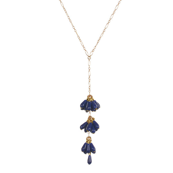 Close-up of delicate gold chain necklace with drop pendant of 3 bunches of dark blue beads with single bead at end.