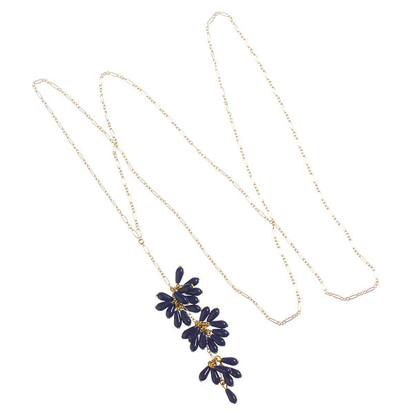 Delicate gold chain necklace with drop pendant of 3 bunches of dark blue beads with single bead at end.