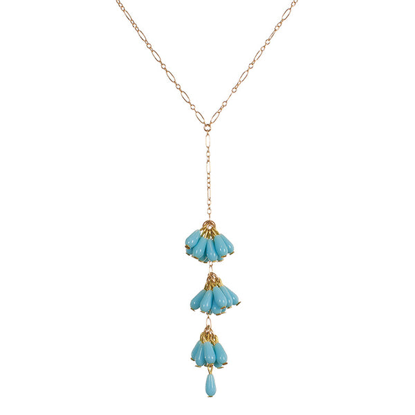 Close-up of delicate gold chain necklace with drop pendant of 3 bunches of turquoise beads with single bead at end.