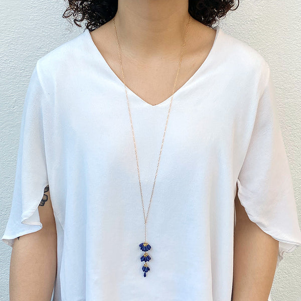 Woman wearing gold chain necklace with pendant of 3 bunches dark blue beads and single bead at end.