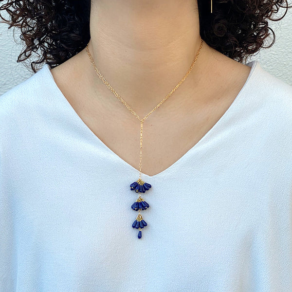 Woman wearing gold chain necklace with pendant of 3 bunches dark blue beads and single bead at end, worn short.